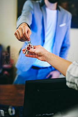 Buy stock photo Cropped shot of an unrecognizable male receptionist handing over a bunch of keys to a female visitor at the front desk of a hotel