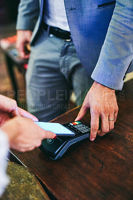 Buy stock photo Cropped shot of an unrecognizable woman making a payment using a smartphone and a card machine at a hotel front desk