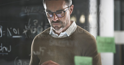Buy stock photo Cropped shot of a handsome mature businessman standing alone in the office and looking at post-its late at night