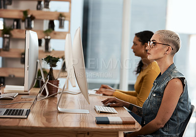 Buy stock photo Shot of an attractive young businesswoman working on a computer with her colleague in the background inside an office