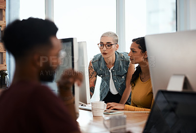 Buy stock photo Shot of two attractive young businesswomen working on a computer together inside a modern office with colleagues in the background