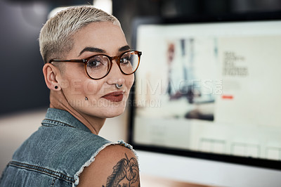 Buy stock photo Portrait of an attractive young creative businesswoman feeling cheerful while working on a computer inside her office