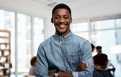 Buy stock photo Portrait of a handsome young businessman posing with his arms folded inside an office with his colleagues in the background