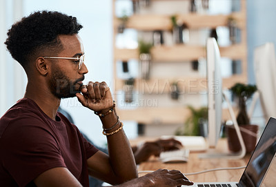 Buy stock photo Shot of a handsome young businessman looking thoughtful while working on his laptop inside an office