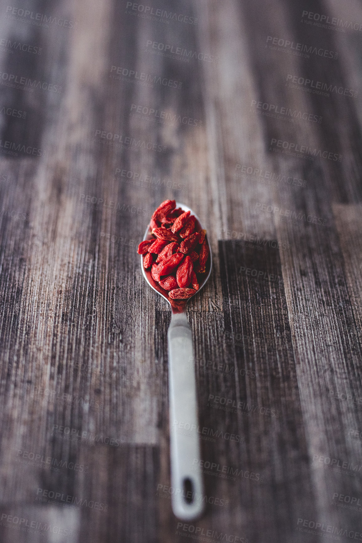 Buy stock photo Shot of goji berries on a spoon against a wooden background