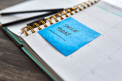 """Buy stock photo Shot of a notebook and sticky note saying """"smile today"""" stuck to it on a desk"""