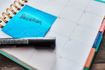 """Buy stock photo Shot of a notebook and a sticky note saying """"vacation"""" stuck to it on a desk"""