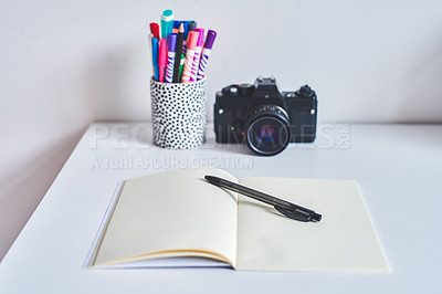 Buy stock photo Shot of a camera, notebook and various other business tools on a desk at home