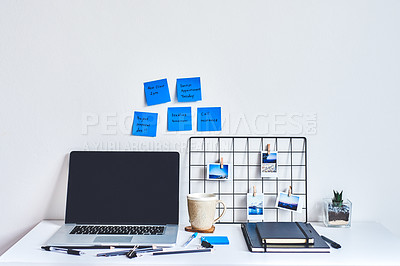 Buy stock photo Shot of a laptop, notebook and smartphone on a work desk with sticky notes on the wall behind it