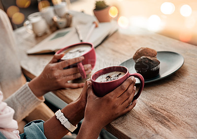 Buy stock photo Cropped shot of two unrecognizable girlfriends having coffee with muffins at a coffee shop during the day