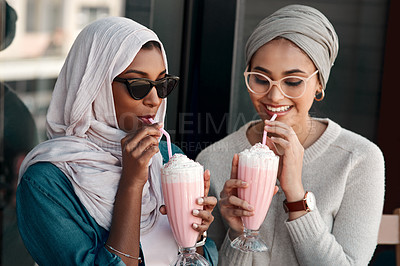 Buy stock photo Cropped shot of two affectionate young girlfriends having milkshakes together in a cafe while dressed in hijab