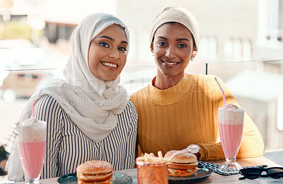 Buy stock photo Cropped portrait of two affectionate young girlfriends having a meal together at a cafe while dressed in hijab