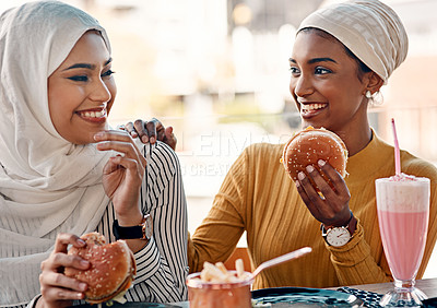 Buy stock photo Cropped shot of two affectionate young girlfriends eating burgers at a cafe while dressed in hijab