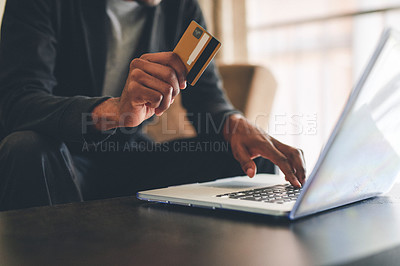 Buy stock photo Cropped shot of an unrecognizable man using a credit card and a laptop to shop online at home