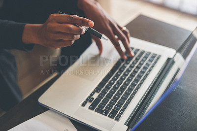 Buy stock photo High angle shot of an unrecognizable man using a laptop while working from home
