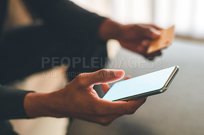 Buy stock photo Cropped shot of an unrecognizable man using a credit card and a smartphone to shop online at home