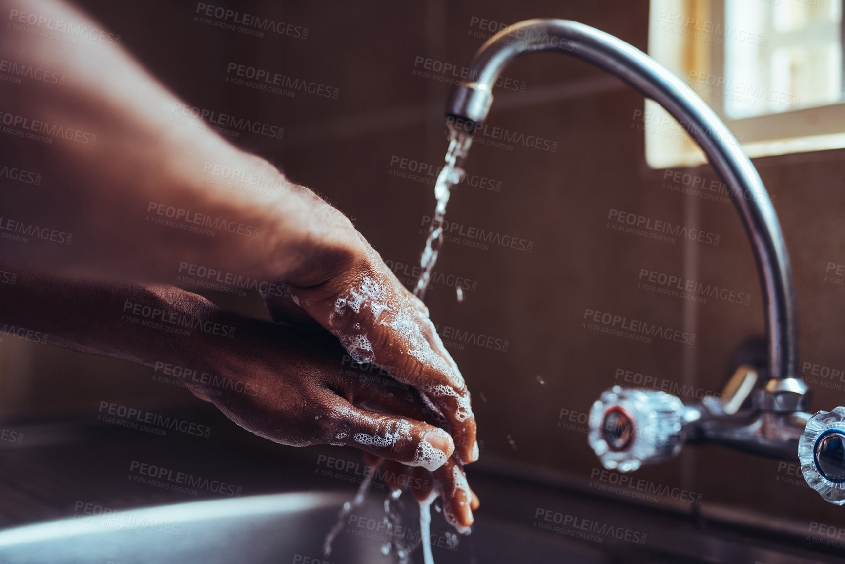 Buy stock photo Cropped shot of an unrecognizable man washing his hands in the kitchen sink at home