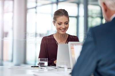 Buy stock photo Shot of a businessman and businesswoman using a laptop while having a discussion in a modern office