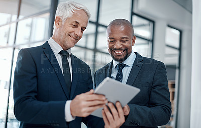 Buy stock photo Shot of two businessmen using a digital tablet together in a modern office