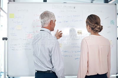 Buy stock photo Shot of a mature businessman and businesswoman having a brainstorming session in a modern office