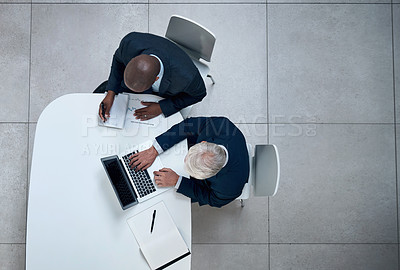Buy stock photo High angle shot of two businessmen working together on a laptop in an office