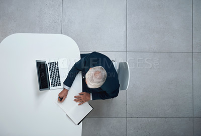 Buy stock photo High angle shot of a mature businessman writing in a notebook while working on a laptop in an office