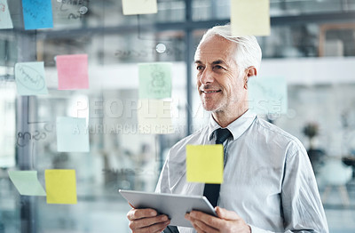 Buy stock photo Shot of a mature businessman using a digital tablet while having a brainstorming session in a modern office