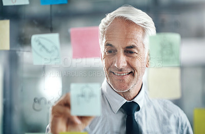 Buy stock photo Shot of a mature businessman having a brainstorming session in a modern office