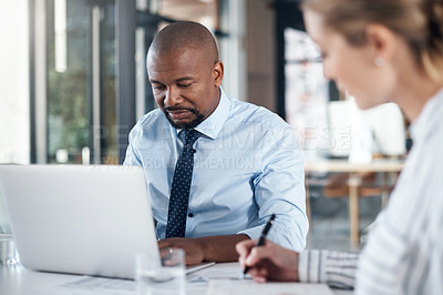 Buy stock photo Shot of a mature businessman working on a laptop alongside a colleague in an office