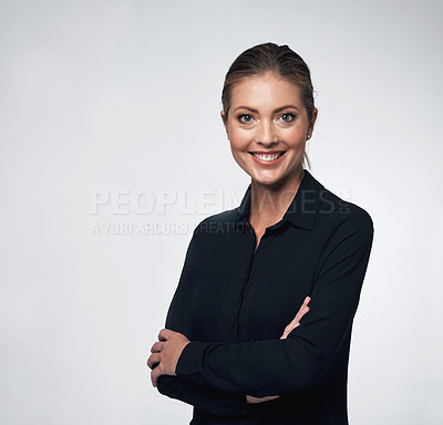 Buy stock photo Portrait of a young businesswoman standing with her arms crossed against a grey background