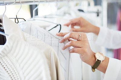 Buy stock photo Cropped shot of an unrecognizable woman looking through a railing of clothing in a boutique