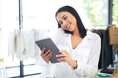 Buy stock photo Shot of a young business owner talking on her cellphone while using a digital tablet in her store