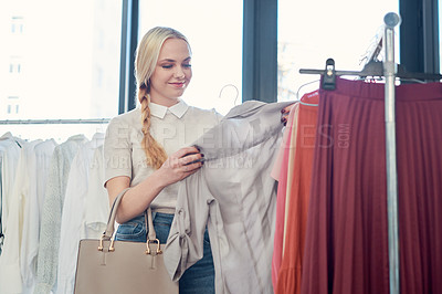 Buy stock photo Shot of a young woman shopping for clothes in a store
