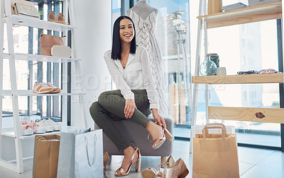Buy stock photo Shot of an attractive young woman fitting on shoes in a boutique
