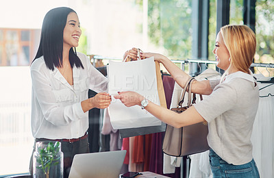 Buy stock photo Cropped shot of a young woman making a purchase in a clothing store