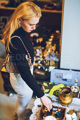 Buy stock photo Shot of a young woman shopping for antique goods at a store
