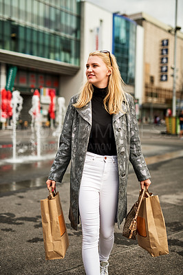 Buy stock photo Shot of a young woman spending a day shopping in the city