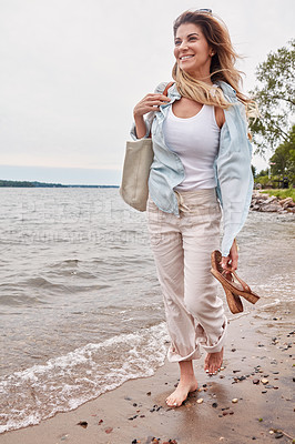 Buy stock photo Shot of a beautiful young woman going for a walk along the waters edge of a lake
