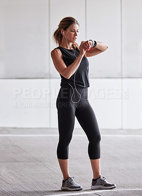Buy stock photo Shot of a sporty young woman checking her watch while exercising outdoors