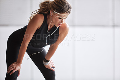 Buy stock photo Shot of a sporty young woman catching her breath while exercising outdoors