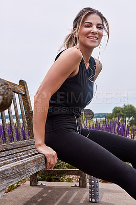 Buy stock photo Portrait of a sporty young woman doing bench dips outdoors