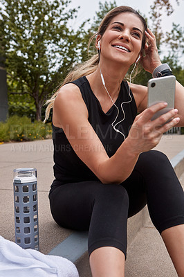 Buy stock photo Shot of a sporty young woman using a cellphone while exercising outdoors