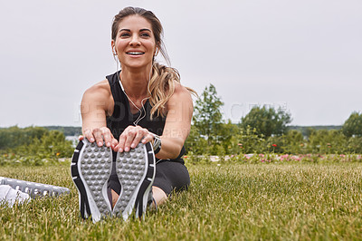 Buy stock photo Shot of a sporty young woman stretching her legs while exercising outdoors