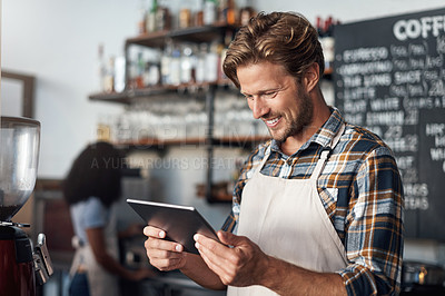 Buy stock photo Cropped shot of a young shop owner using a digital tablet while standing in his cafe