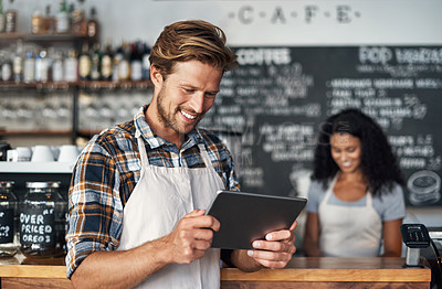 Buy stock photo Defocused shot of a young shop owner using a digital tablet while standing in his cafe