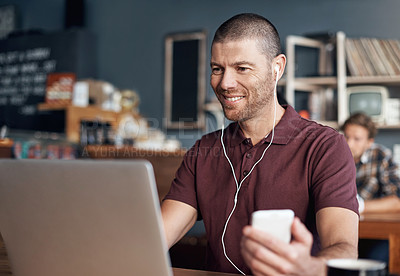 Buy stock photo Shot of a man using his cellphone and laptop in a cafe
