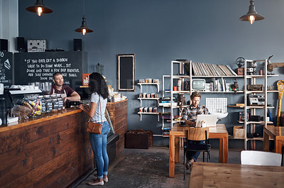 Buy stock photo Shot of a barista serving a customer in a cafe