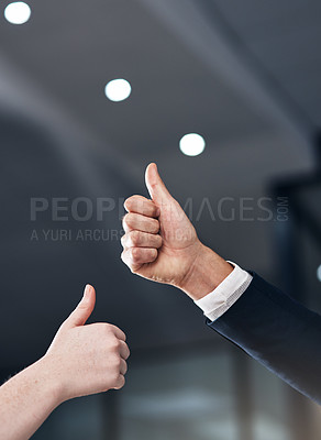 Buy stock photo Cropped shot of two businesspeople giving thumbs up in a modern office