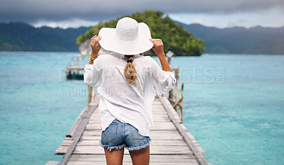 Buy stock photo Rearview shot of an unrecognizable woman standing on a boardwalk overlooking the ocean during vacation