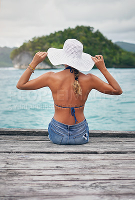 Buy stock photo Rearview shot of an unrecognizable woman sitting on a boardwalk overlooking the ocean during vacation